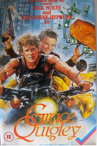 Pictured is the 1980s UK video cover art of the film depicting a surly looking Nick Nolte riding a motorcycle wearing a vest with accentuated muscles. Behind him on teh bike is Katehrine Hepburn brandishing a gun and bag full of money. Behind them is a cityscape of skyscrapers and the illustration seems to express a madcap adventure.